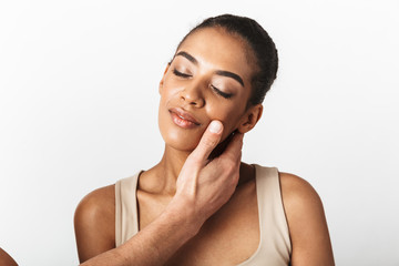 African woman posing isolated over white wall background while someone's hand touching her neck.