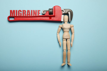 Wooden figure of man with his head clamped in vice with inscription migraine. Pain, stress, headache.