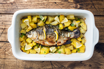 Baked fish carp with potatoes in a ceramic pan. Rustic style.