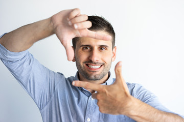 Cheerful guy wearing casual, gesturing at camera. Young Caucasian man with stubble showing frame with fingers. Portrait or photograph concept