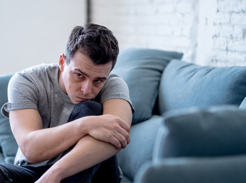 Young man suffering from depression lying on sofa alone at home feeling frustrated and hopeless