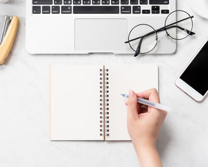 A woman is writing notes isolated on stylized marble office working desk with smartphone, laptop, glasses and coffee, mock up, topview, flatlay, copyspace, closeup