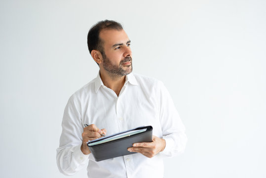 Pensive handsome man holding file and writing. Business man thinking and working. Paperwork concept. Isolated front view on white background.