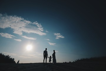 Silhouette portrait of beautiful young family in expectation of newborn. Man and woman standing face to face with their daughter over sunset sky. Background in evening in scenic nature landscape