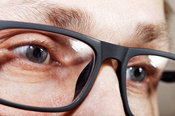 Closeup photo of human eyes with glasses. Shallow focus.