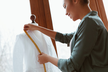 Wall Mural - Young designer with tape is measuring white shirt. Side view