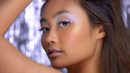 thai asian model in studio with silver rain disco background and party makeup Blowing hai