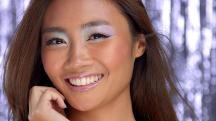 thai asian model in studio with silver rain disco background and party makeup smiling