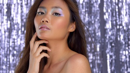 thai asian model in studio with silver rain disco background and party makeup touching her ideal skin
