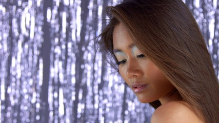 thai asian model in studio with silver rain disco background and party makeup watchuing down