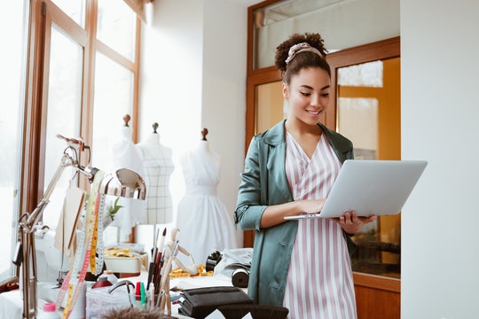 Online orders by email. Young woman tailor with laptop is answering emails
