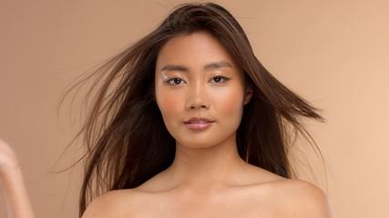 thai asian japanese model closeup portrait with hair blowing out. Simmetrical portrait
