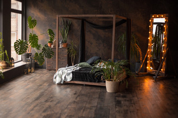 loft style dark bedroom with green plants and textured wall