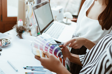 Wall Mural - Close-up of young designer with client are choosing colors for dress.