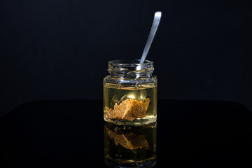 Fototapeta truffle mushroom in a jar of honey on a black background. Minimalism in composition. Luxury food. Free space for text.