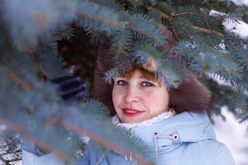 a woman in a hat with earflaps and a light jacket among the branches of a blue spruce