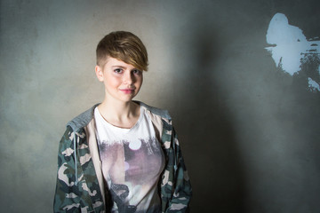 Young girl with short haircut concrete wall on background
