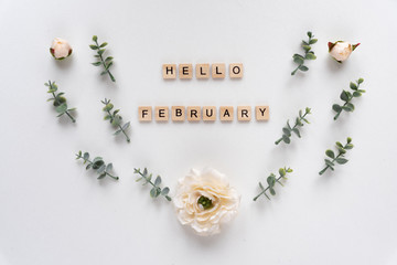 Hello February words on white marble background.