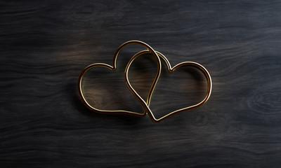 Herzförmige Ringe liegen auf dunklem Holztisch