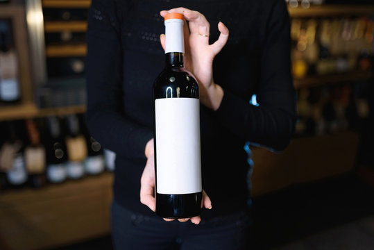 bottle of red wine in hands of woman