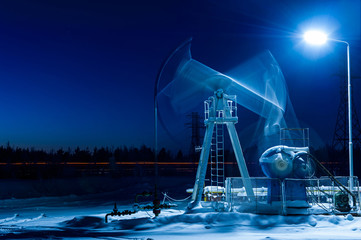 Working oil pump at night time. Oilfield during winter. Oil and gas concept. Motion blur.