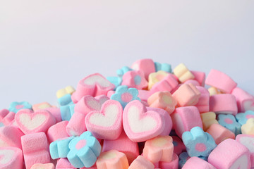 Pair of Pink and White Heart Shaped Marshmallow on the Pile of Pastel Color Flower Shaped Marshmallow Candies with Free Space for Text and Design