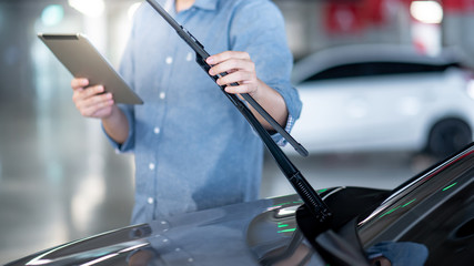 Male auto mechanic holding digital tablet checking windshield wiper in auto service garage. Mechanical maintenance engineer working in automotive industry. Automobile servicing and repair