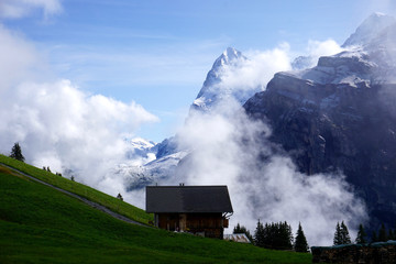 mountain hut and snowy peaks