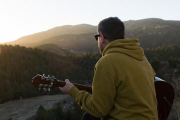 Hombre tocando la guitarra mirando a la puesta de sol en las montañas