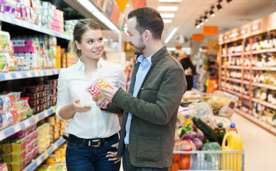 Family couple is looking food for home in the supermarket