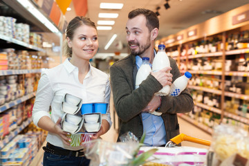Smiling couple with products in milk department