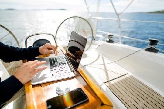Digitaler Nomade mit Laptop arbeitet auf einem Segelboot
