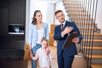 handsome broker showing something to attractive woman standing with daughter
