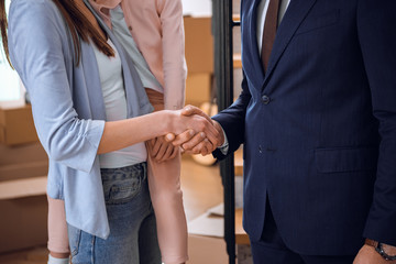 cropped view of woman shaking hands with broker while holding in arms daughter