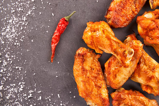 Chicken wings with red hot chili pepper and salt on a black slate in background. Directly above.