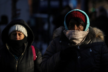 Morning commuters walk to work, as record low temperatures spread across the Midwest and Eastern states, in New York