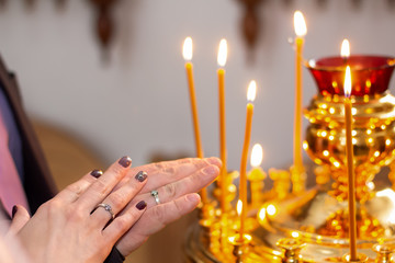 Rings, dressed in the hands of the newlyweds, against the background of church candles close-up.