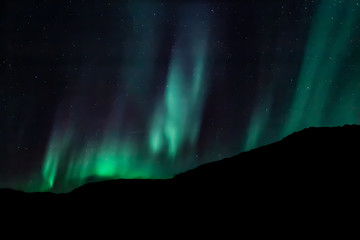Amazing Aurora Borealis in North Norway (Ringvassoy), mountains and sea in the background