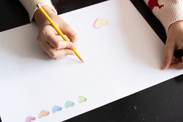 girl draws a pencil heart on paper. handmade DIY Valentine's Day card