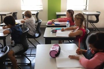 Kids studying in classroom sitting at desks in school