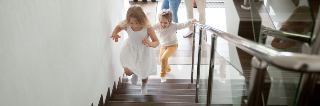 Happy kids go upstairs to second floor their new modern house, family moving day relocation and loan, buy first home concept. Horizontal photo banner for website header design with copy space for text