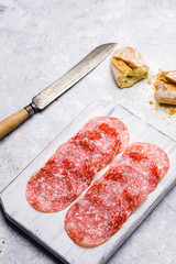 italian salami on small cutting board on delicate background