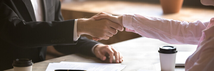 Horizontal photo close up hands two people businessman businesswoman shake hands, make good deal, hr manager greeting new employee hiring, services and client concept, banner for website header design