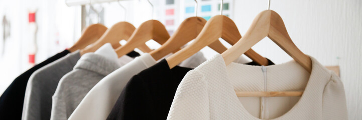 Close up photo stylish fashion white grey black colors women clothes choice at designer store hang on wooden hangers rack rails, dressmaking tailoring sewing concept, banner for website header design