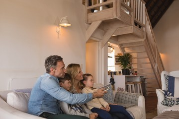 Family watching television in living room at home