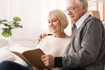 Happy elderly couple looking at photo album together