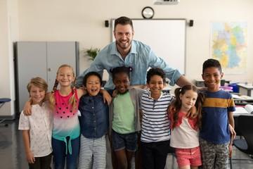 Happy school kids and teacher standing classroom
