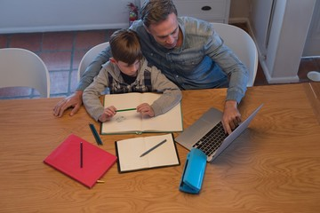 Father helping his son with his homework while using laptop