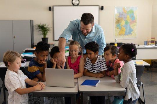 Male teacher teaching kids on laptop in classroom