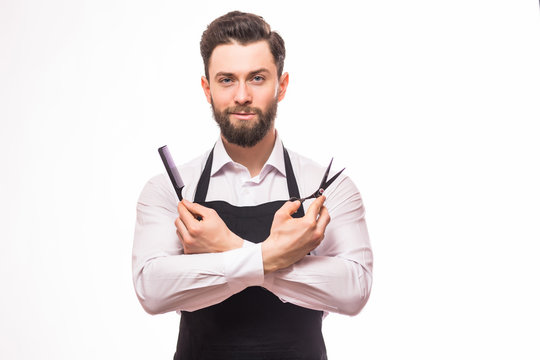 Portrait of bearded barber holding equipments in hand, looking at camera, isolated on white background